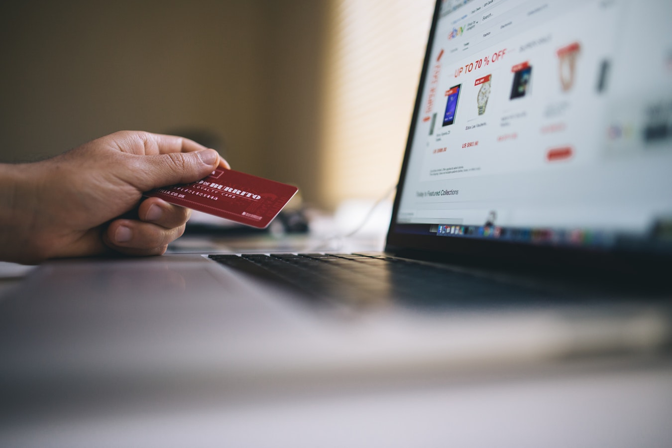 laptop i karta kredytowa w ręce