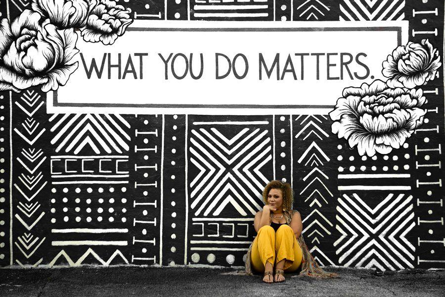 kobieta siedzi pod murem z napisem